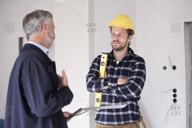 Architect and construction worker discussing while standing in constructing home