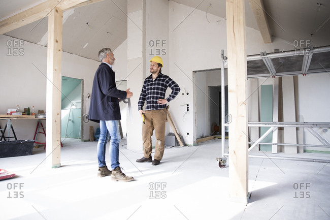 Architect and construction worker discussing while standing in renovating house