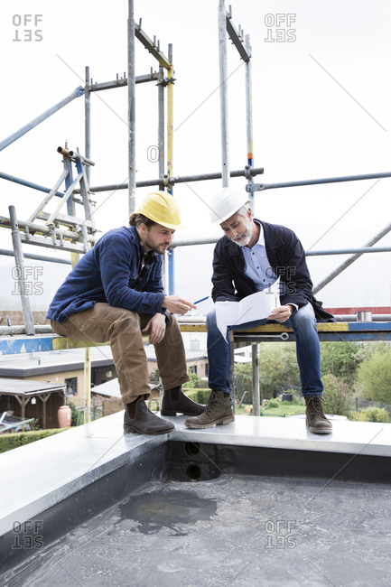 Architect and construction worker discussing blueprint while sitting on scaffold against clear sky