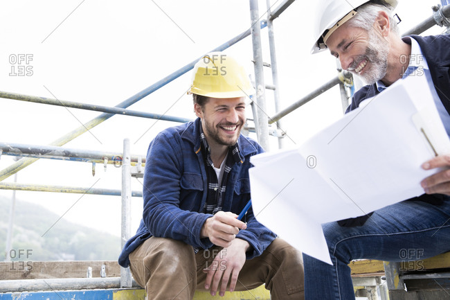 Smiling architect and construction worker discussing blueprint while sitting against clear sky at construction site