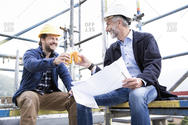 Architect and construction worker toasting drinks while sitting against clear sky at construction site