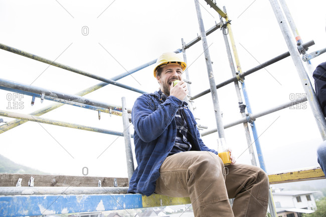Construction worker eating food while sitting against clear sky at construction site