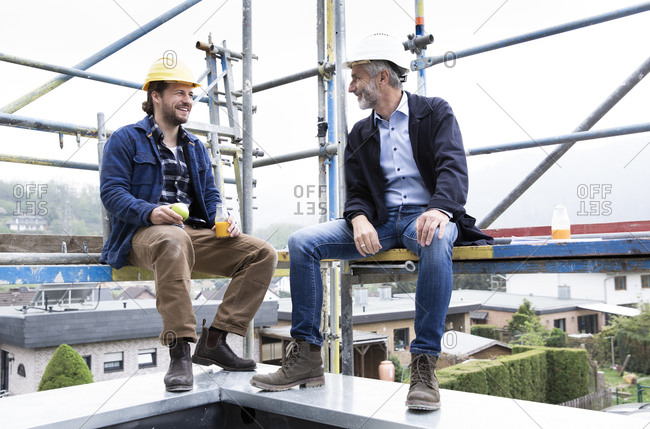 Architect and construction worker talking while sitting at construction site