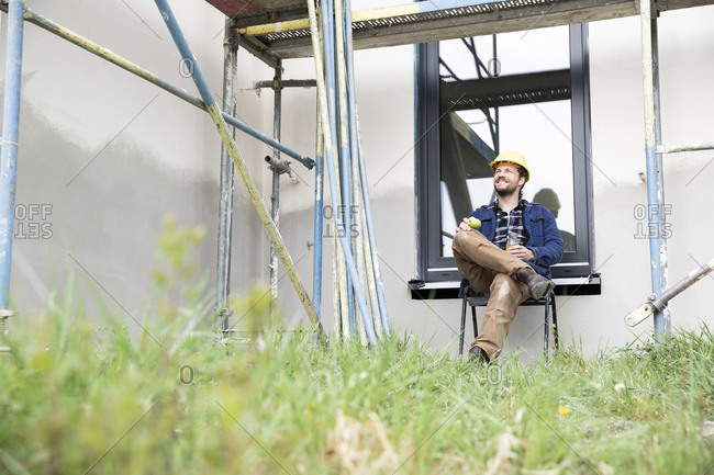 Thoughtful construction worker holding fruit while sitting against window at construction site