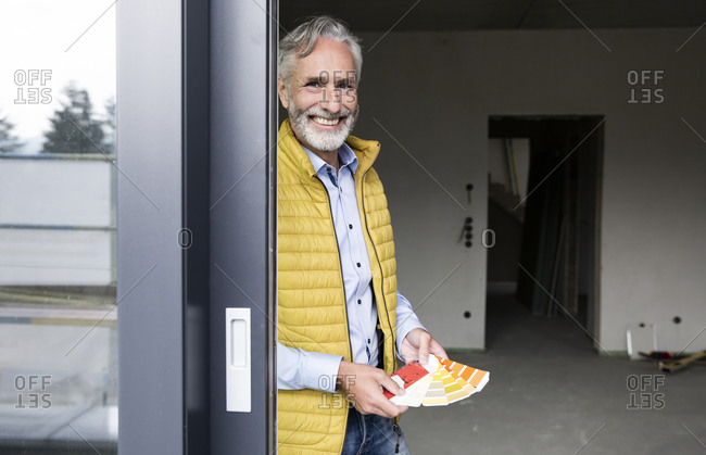 Smiling male architect holding color swatch in renovating house seen through window