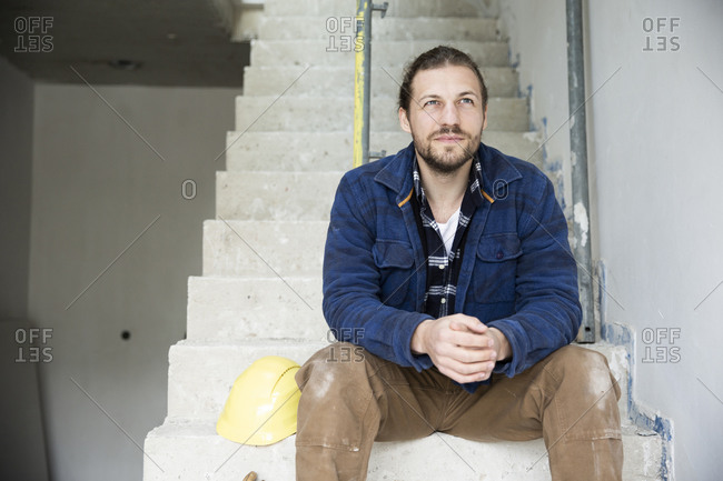 Thoughtful construction worker sitting on steps in house under construction