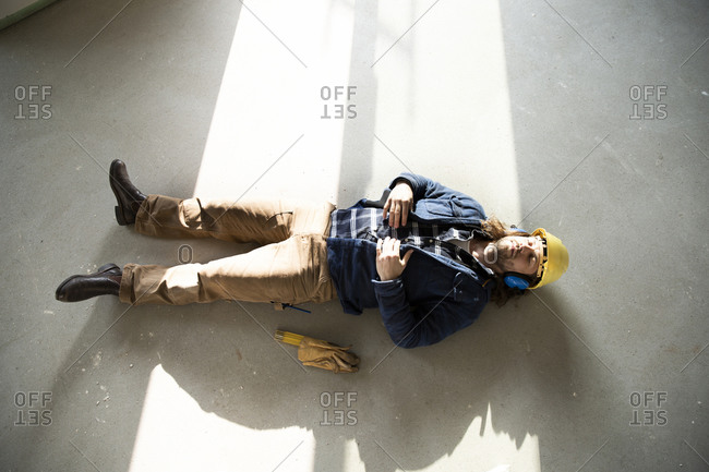 Construction worker sleeping on floor in renovating house