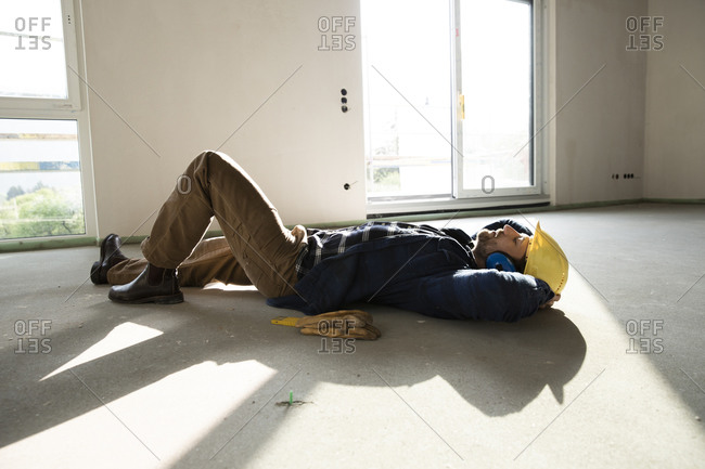 Construction worker with hands behind head sleeping on floor in house under construction