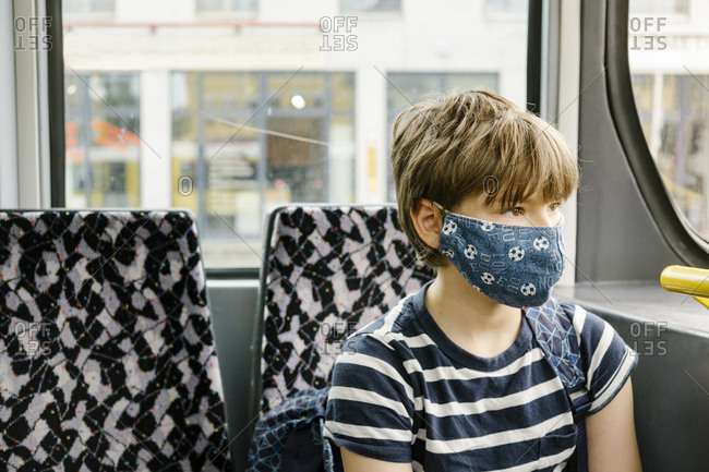 Boy wearing protective mask in tram