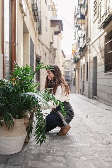 Female florist placing plants outside flower shop while kneeling on street against buildings