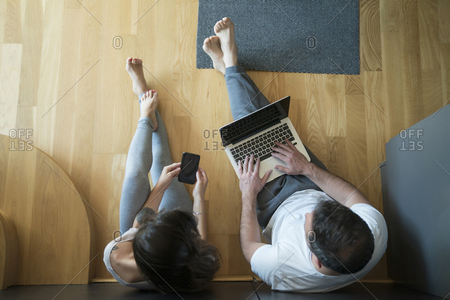 Man working over laptop while woman using smart phone on hardwood floor at home