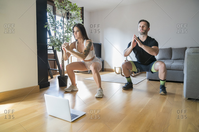 Couple exercising on hardwood floor at home