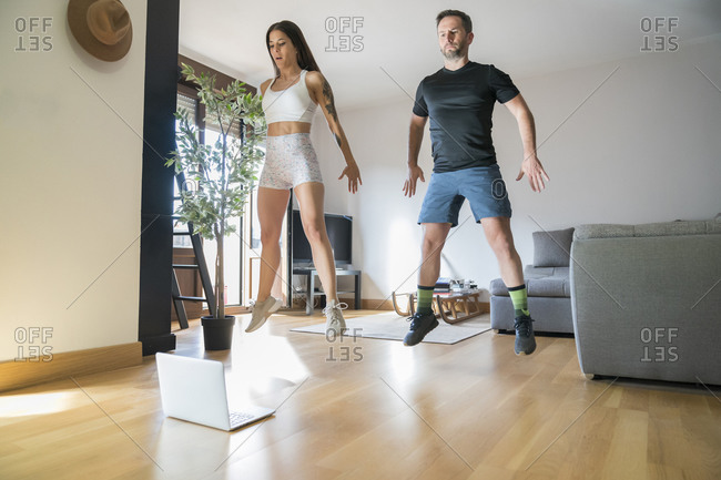 Couple jumping while exercising on hardwood floor at home