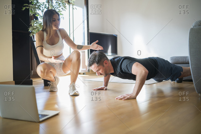 Woman motivating man in doing push-ups on hardwood floor at home