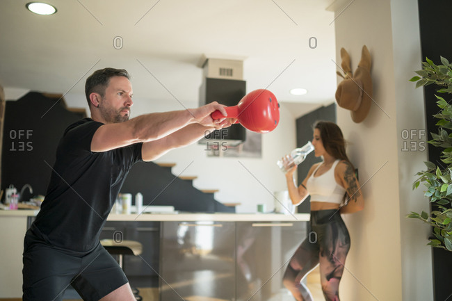 Man exercising with kettlebell while woman drinking water in background at home