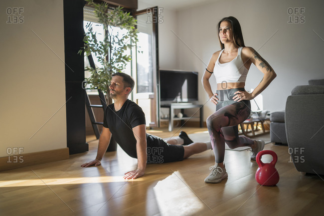 Couple exercising on floor in living room at home