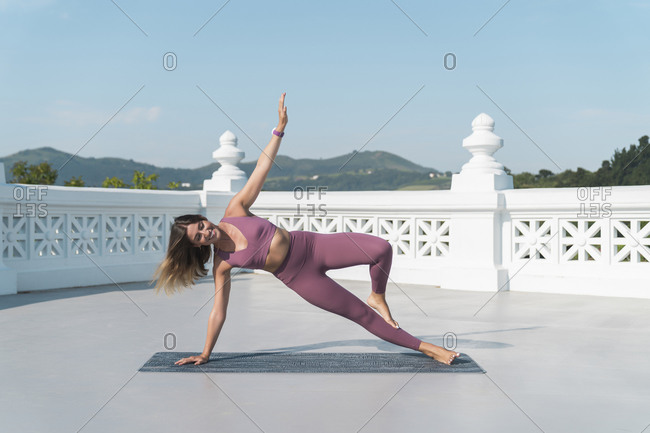 Young woman practicing side plank pose on building terrace against sky