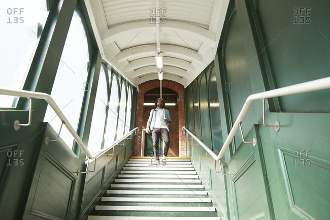 Young trendy man moving down steps at railroad station