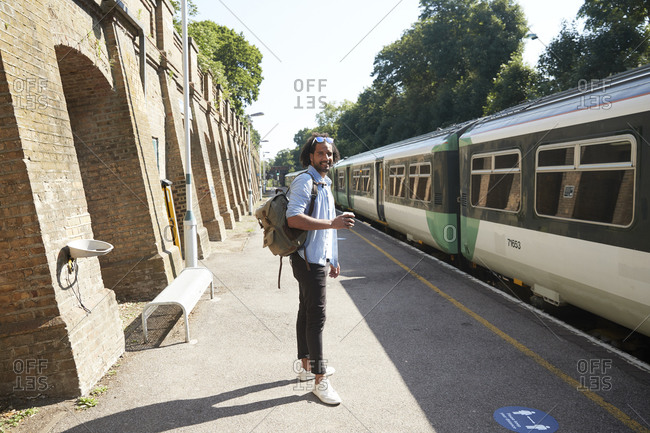 Young trendy man standing at railroad station platform during sunny day