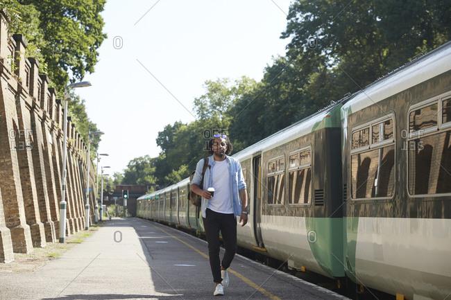 Young trendy man walking at railroad station platform during sunny day
