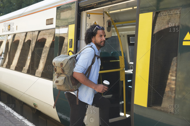 Young trendy man boarding train at railroad station
