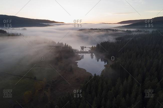 Germany- Baden-Wurttemberg- Drone view of Schluchsee lake shrouded in thick fog at sunrise