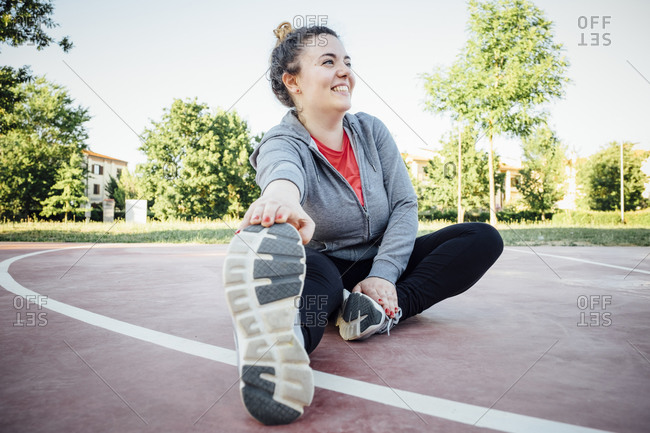 Female jogger stretching her leg on racetrack