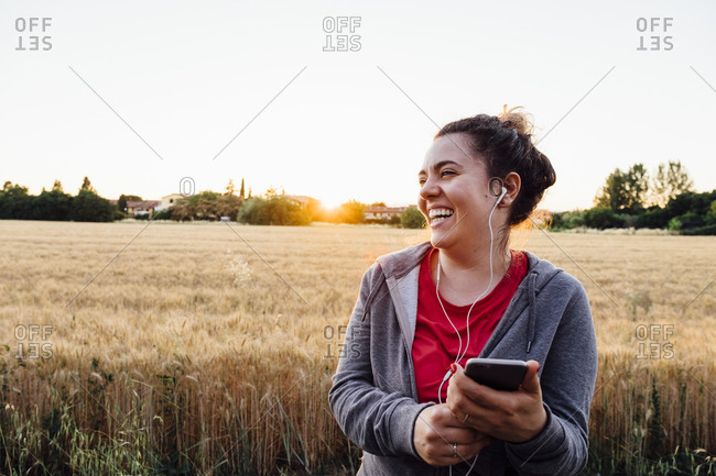 Woman jogging and listening to music with smartphone at sunset