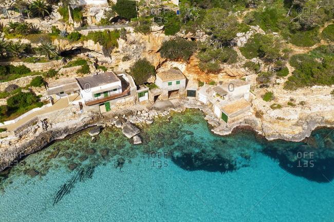 Spain- Mallorca- Santanyi- Drone view of boathouses on rocky coast of Mallorca
