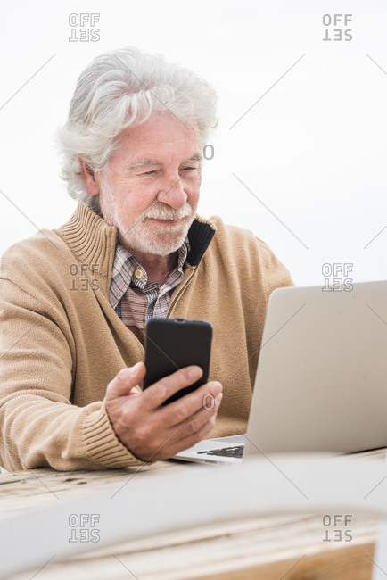 Senior man holding smart phone while using laptop at table