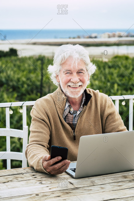 Smiling senior man holding smart phone while sitting with laptop at table