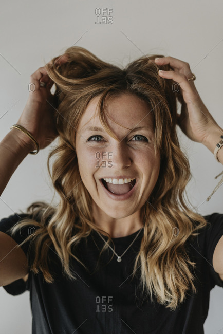 Close-up of cheerful woman with hands in hair screaming against wall