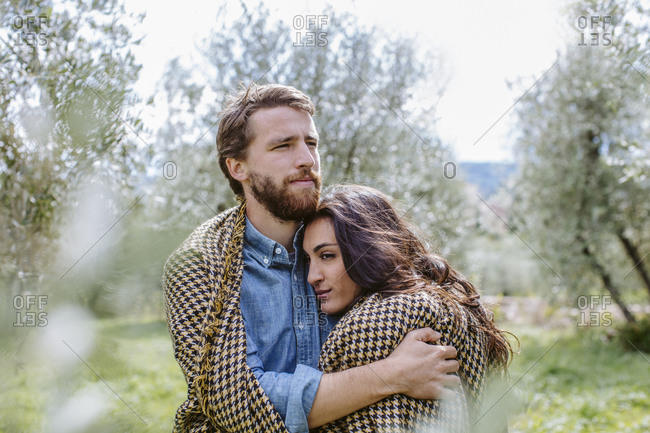 Loving young couple embracing while standing against trees