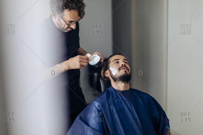 Barber applying shaving cream on client in salon