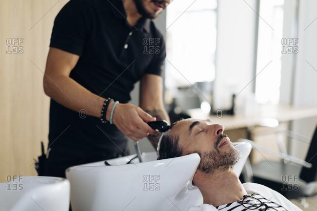 Hairdresser washing client's hair at salon