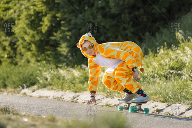 Beautiful young woman in yellow costume while skateboarding on road during sunny day