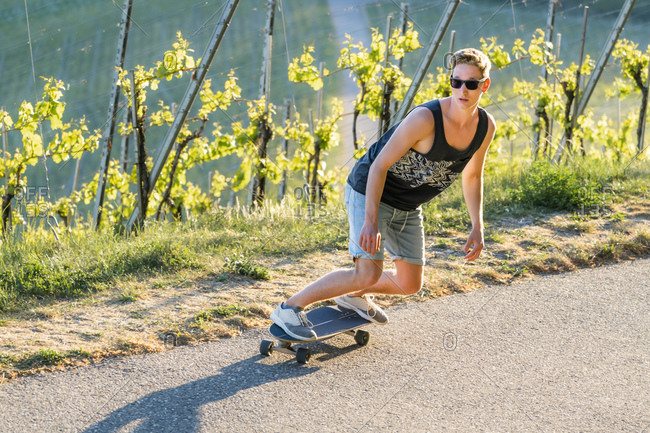 Handsome young woman skateboarding on road during sunny day