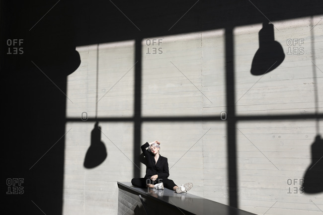 Female professional wearing elegant suit relaxing on retaining wall with sunlight and shadow in background