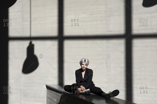 Female professional wearing black suit relaxing against sunlight and shadow in background at office
