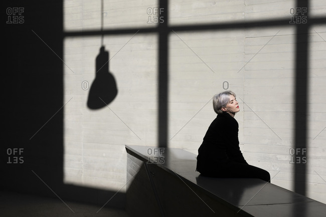 Female professional wearing black suit relaxing on retaining wall with sunlight and shadow in background at office