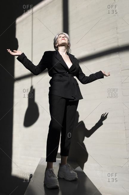 Female professional wearing stylish suit standing on retaining wall with sunlight and shadow in background