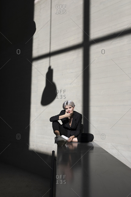 Stylish female professional wearing suit relaxing on retaining wall with sunlight and shadow in background