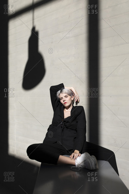 Stylish female professional wearing elegant suit sitting with sunlight and shadow in background at office