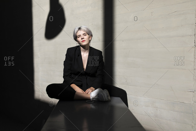 Stylish female professional wearing elegant black suit sitting against wall in office