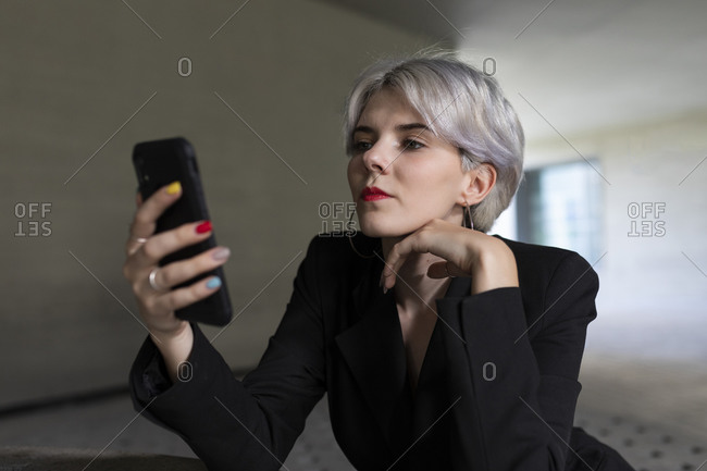 Close-up of businesswoman wearing black suit using smart phone while sitting in office