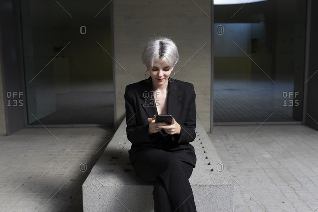 Female professional wearing elegant suit using smart phone while sitting on seat in office