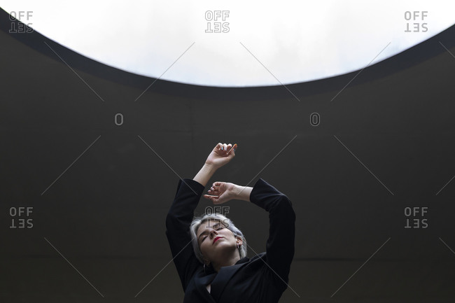 Stylish female professional wearing elegant suit standing against illuminated light in office