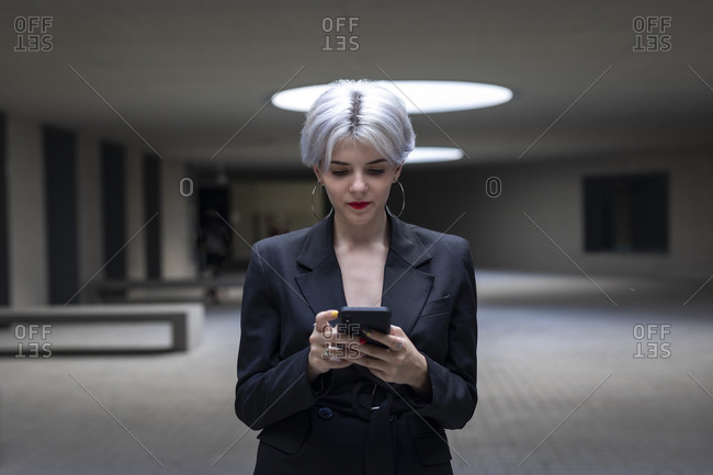 Female professional wearing elegant suit using mobile phone while standing in office