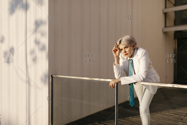 Young woman wearing white suit standing by railing against built structure