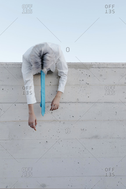 Young woman wearing blue tie climbing on retaining wall against clear sky